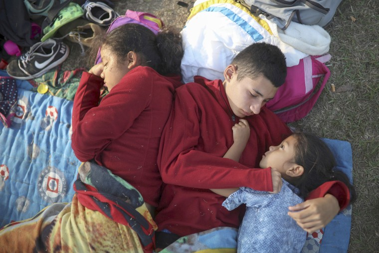 """The Zelaya siblings, from El Salvador, huddle together on a soccer field at the sports club where Central American migrants traveling with the annual \""""Stations of the Cross\"""" caravan are camped out, in Matias Romero, Oaxaca State, Mexico on April 4. The children's father Elmer Zelaya, 38, said the family is awaiting temporary transit visas that would allow them to continue to the U.S. border, where they hope to request asylum and join relatives in New York.  President Donald Trump's comments have confused and befuddled the migrant families that are traveling with the caravan, some of whom never intended on going all the way to the United States after the end of the \""""Stations of the Cross\"""" journey. It is a symbolic event held around Easter each year to raise awareness about the plight of migrants and has never left southern Mexico, though some participants then continue north on their own."""