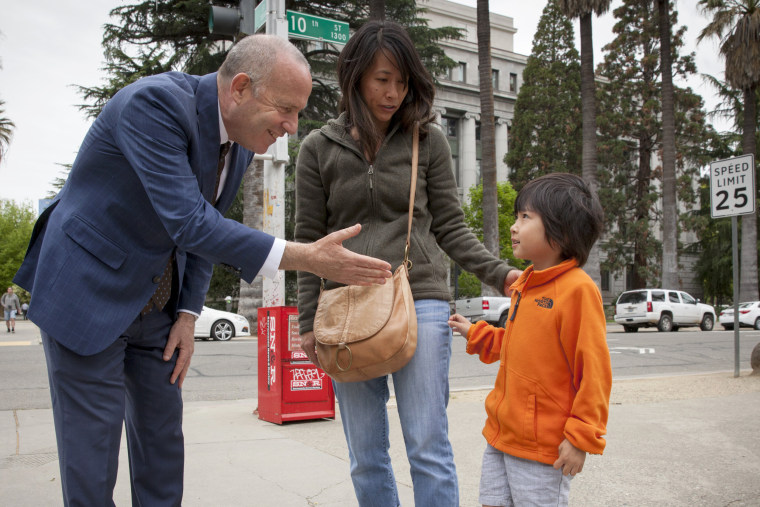 Image: Sacramento Mayor Darrel Steinberg introduces himself to Thuy Dao's (center) son Ellis, 5, after meeting them on the street in Sacramento, California, on April 5, 2018.