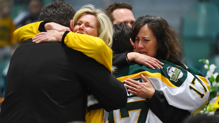 Image: Mourners comfort each other at a vigil to honor Humboldt Broncos members who died in fatal bus accident.