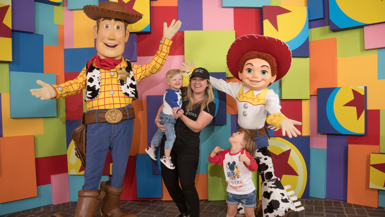 "Kelly Clarkson and her kids take a photo with ""Toy Story"" characters at Disneyland's Pixar Fest"