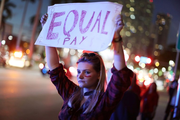 Image: A women holds a sign reading 'Equal Pay'