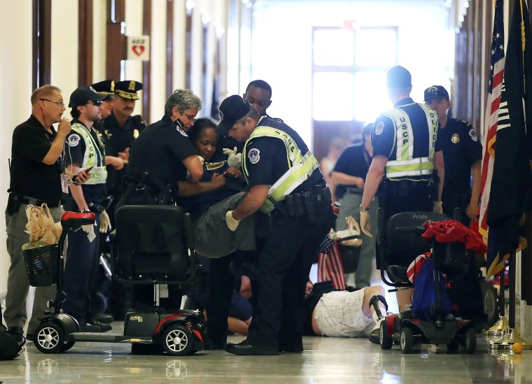 Image: U.S. Capitol Police remove protesters from in front of the office of Senate Majority Leader Mitch McConnell