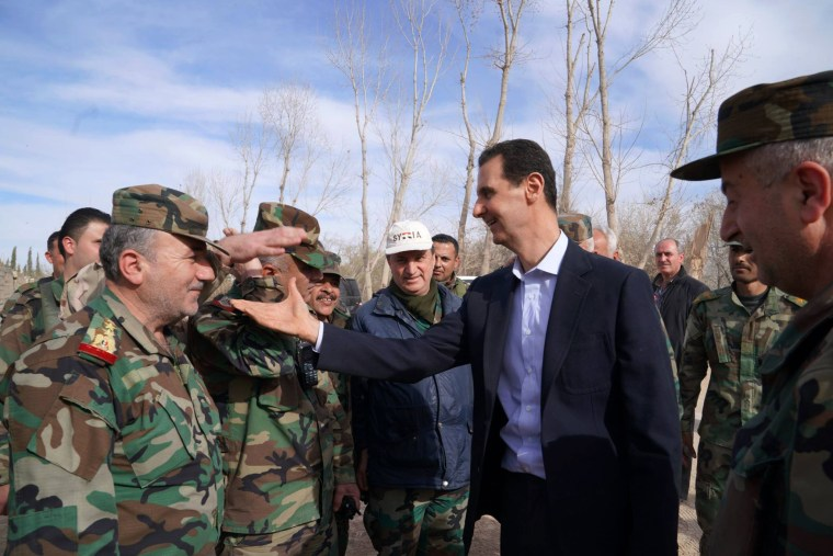 Image: Syrian President Bashar al-Assad shakes hands with government troops in Eastern Ghouta