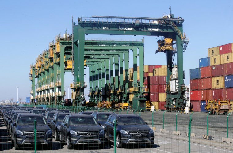 Image: Imported Mercedes Benz cars are seen next to containers at Tianjin Port