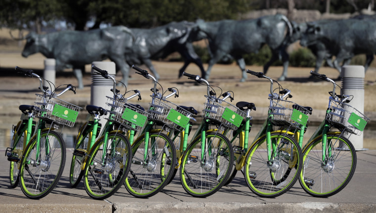 Image: Shared bikes are lined up on a sidewalk by a popular tourist destination in Dallas