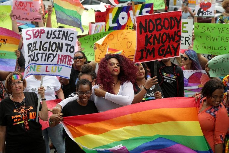 Image: Members of the LGBT community demonstrate outside the Hall of Justice in Port-of-Spain