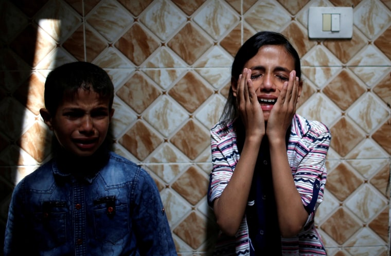Image: Palestinian relatives of Hamas gunman Mohammed Hejelah, who was killed in an Israeli air strike, mourn during his funeral in Gaza City