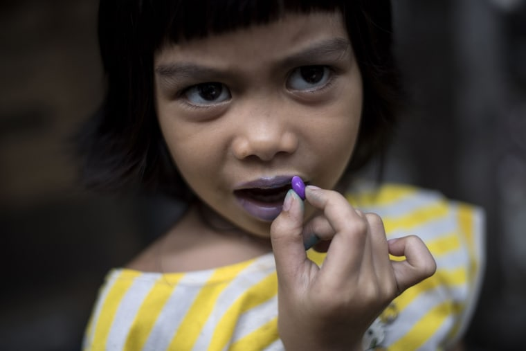 Image: A child uses a candy to color her lips in Manila