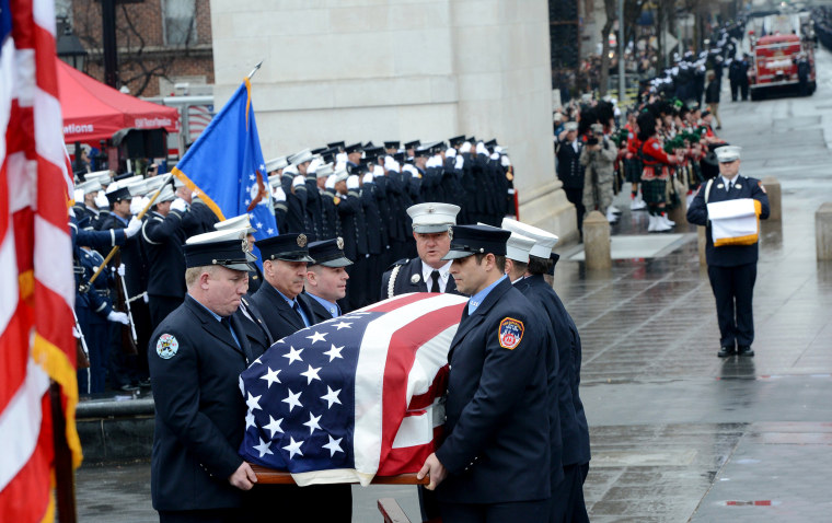 """Image: FDNY honor guard carry the flag-draped coffin of FDNY Fire Marshal Capt. Christopher """"Tripp"""" Zanetis during his funeral in Washington Square Park on March 29, 2018 in New York City."""
