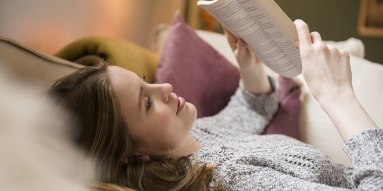 Woman laying on sofa reading book