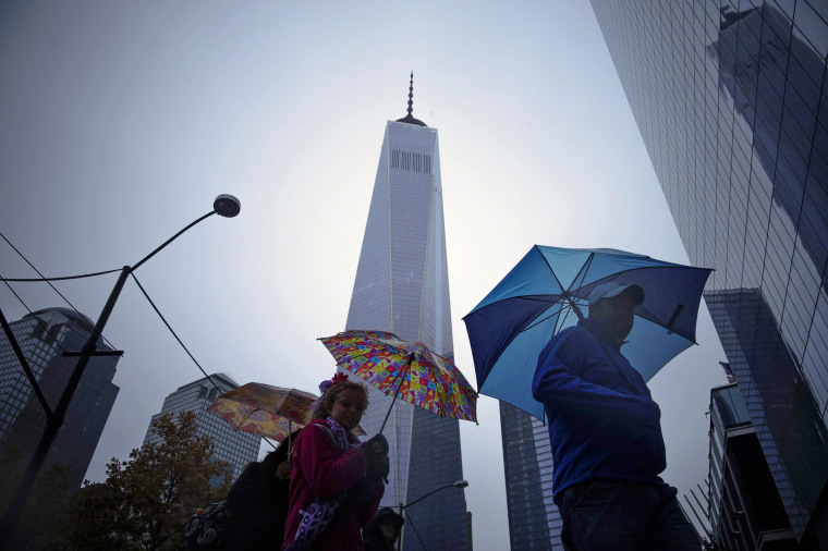 Image: People walk next to the One World Trade Center in New York