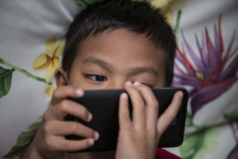 Image: A child looks at a mobile phone