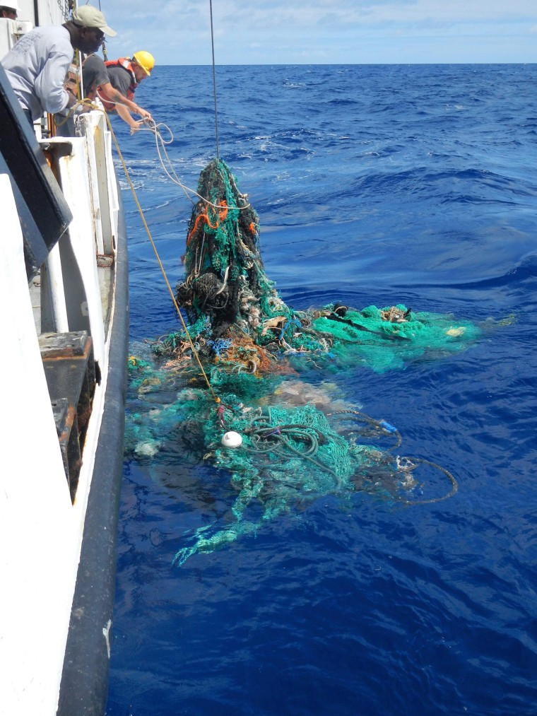 Image: Mega Expedition mothership R/V Ocean Starr crew pull a ghost net from the Pacific Ocean