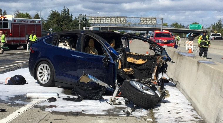 Image: Rescue workers attend the scene where a Tesla electric SUV crashed into a barrier on U.S. Highway 101 in Mountain View