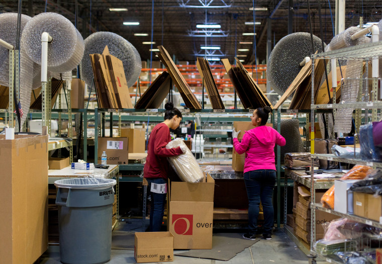 Image: Employees pack merchandise at an Overstock.com warehouse