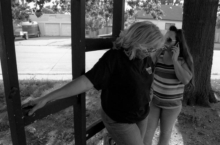 Image: Antonia Correa, leftm waits while Athena Ramos makes a phone call in Grand Island, Nebraska