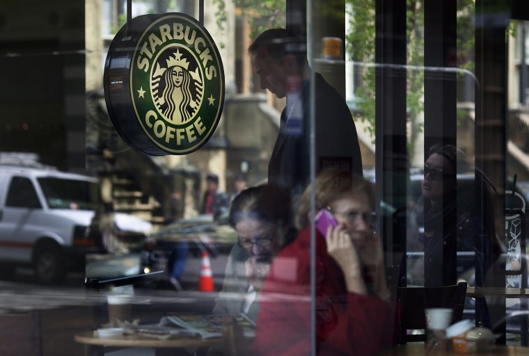 Image: Customers sit inside of a Starbucks Corp. store in New York