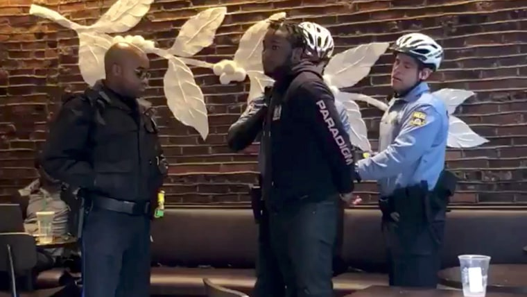 Image: Police officers detain a man inside a Starbucks cafe in Philadelphia