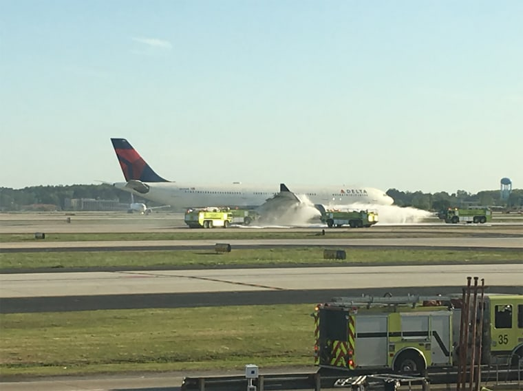 Image: Delta Airlines flight 30 fire being put out by firefighters after landing safely.