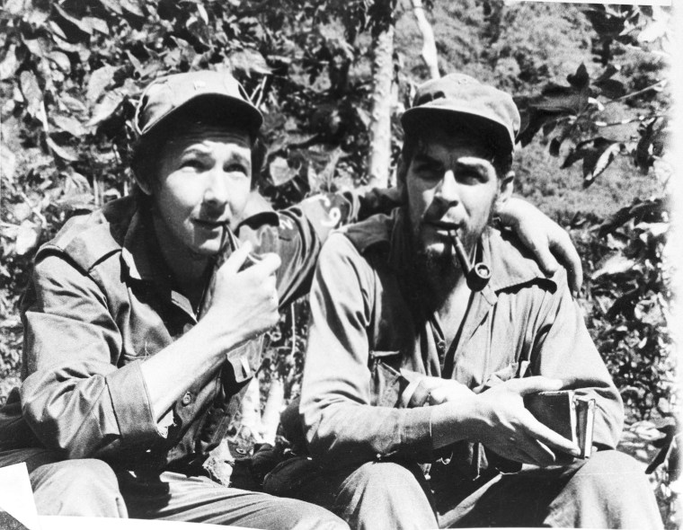 Raul Castro smokes a pipe with Chief Lieutenant Ernesto 'Che' Guevara in their Sierra Cristal mountain stronghold in eastern Cuba, April 1958.