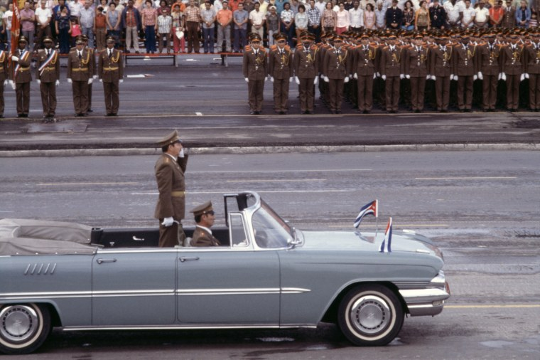 Raul Castro waves from a car while riding through Havana, in a military parade, May 1978.