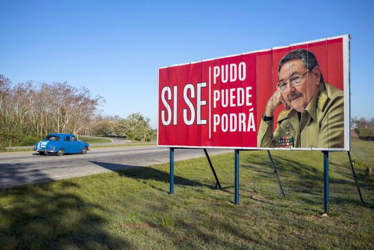 """A car drives by a billboard that reads 'It was, is and will be done,\"""" with a picture of Cuba's then-President Raul Castro on the outskirts of Havana, on April 18, 2018, as Cuba's legislature opened the two-day session to elect a successor to President Castro."""