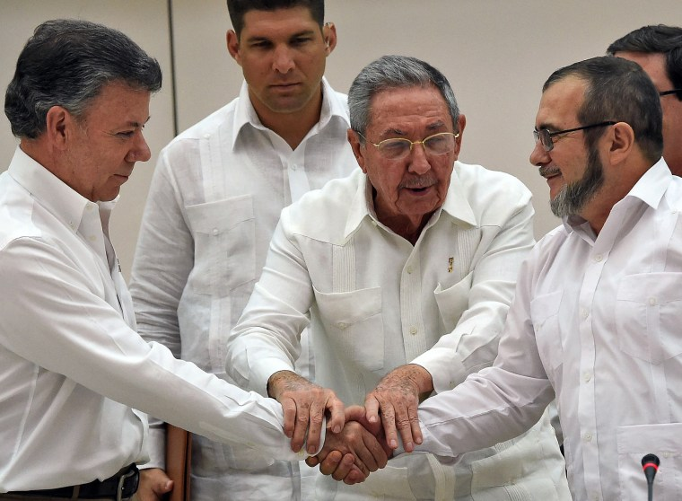 Colombian President Juan Manuel Santos, left, and the head of the FARC guerrillas Timoleon Jimenez, known as Timochenko, right, shake hands as Cuban President Raul Castro holds their hands during a meeting in Havana on Sept. 23, 2015.