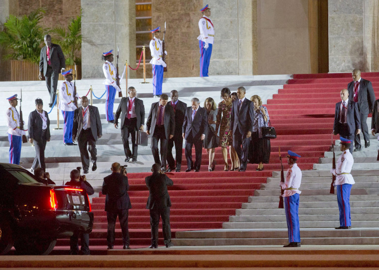 Then-President Obama and first lady Michelle Obama walk with Raul Castro after attending a State Dinner at the Palace of the Revolution, on March 21, 2016, in Havana.