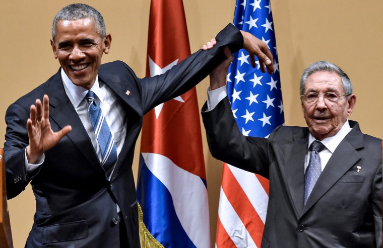 """Raul Castro raises Obama's hand during a meeting at the Revolution Palace in Havana on March 21, 2016. Cuba's Communist president stood next to Barack Obama and hailed his opposition to a long-standing economic \""""blockade,\"""" but said it would need to end before ties are fully normalized."""