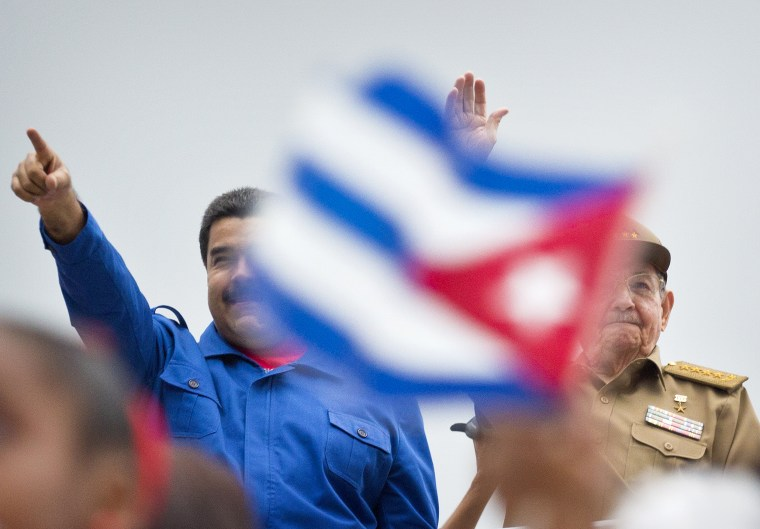 Venezuela's President Nicolas Maduro and Raul Castro, acknowledge marchers as they parade past, marking May Day in Revolution Square, in Havana, May 1, 2015.