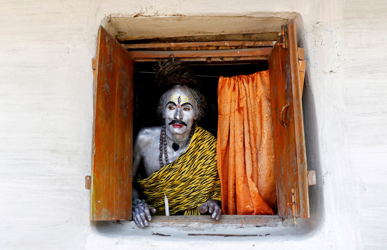 Image: A devotee, dressed as Hindu God Shiva, looks out from a window as he waits to perform during the annual Shiva Gajan religious festival on the outskirts of Agartala