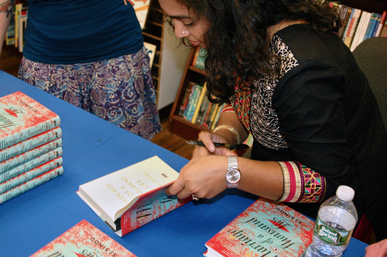 "Image: SJ Sindu signs copies of her novel, ""Marriage of a Thousand Lies."""