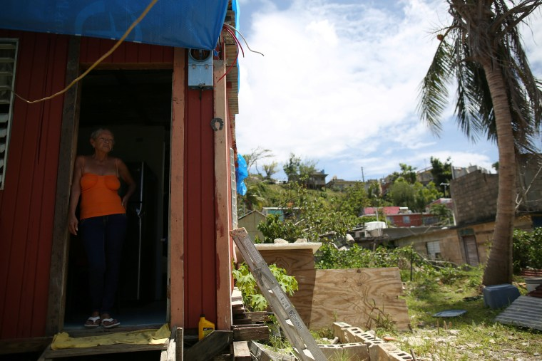 Image: Bexaida Torres stands in the door of what is left of her home after Hurricane Maria