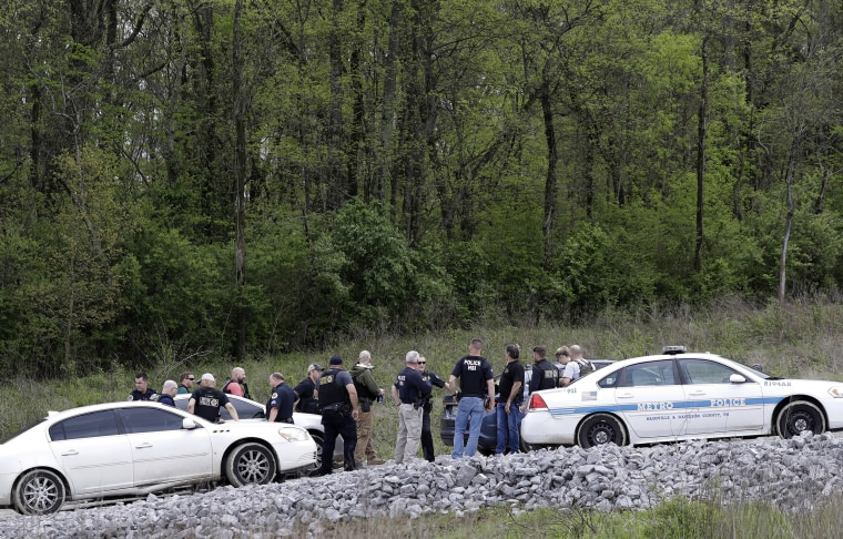 Image: Police gather on a road along a wooded area where Waffle House shooting suspect Travis Reinking was captured
