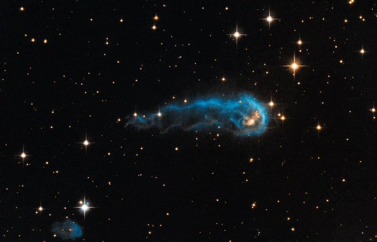 "This light-year-long knot of interstellar gas and dust resembles a caterpillar on its way to a feast. But the meat of the story is not only what this cosmic caterpillar eats for lunch, but also what's eating it. Harsh winds from extremely bright stars are blasting ultraviolet radiation at this ""wanna-be"" star and sculpting the gas and dust into its long shape.