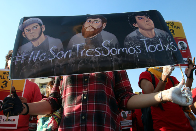 Image: A student holds a placard during a protest to demand the safe return of three film students who went missing on Monday in Guadalajara
