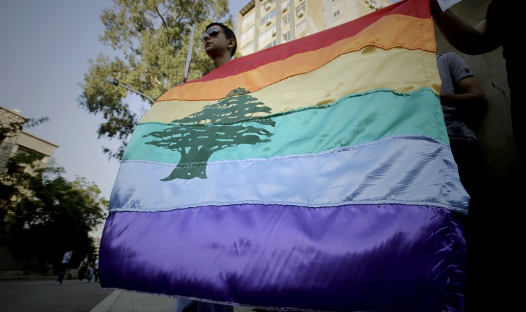 Image: Human rights activists hold a gay pride flag bearing the cedar tree during an anti-homophobia rally in Beirut