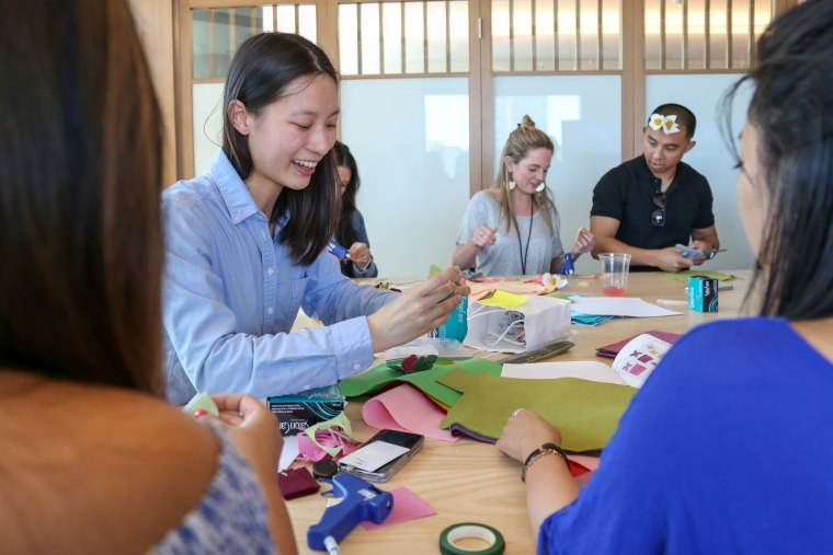 Pinterest software engineer Kim Toy (left) leads her fellow Pinterest employees in a lesson about making flower crowns and lapels out of colorful felt and hot glue.