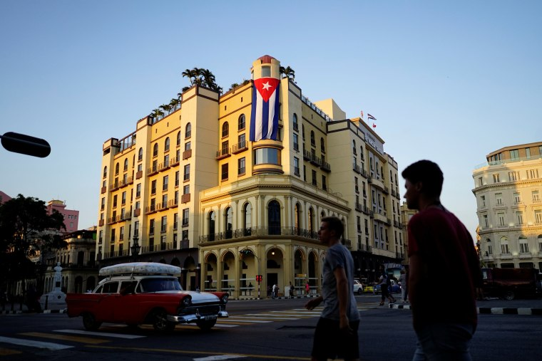Image: A Cuban flag hangs outside a hotel in Havana