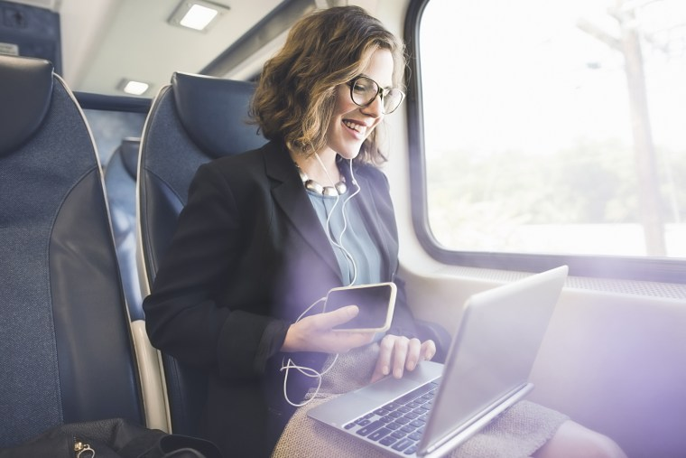 Mid adult woman on train, using smartphone and laptop
