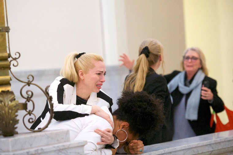 Image: Bill Cosby accusers Caroline Heldman, Lili Bernard and Victoria Valentino (R) react after the guilty on all counts verdict was delivered in the sexual assault retrial at the Montgomery County Courthouse in Norristown