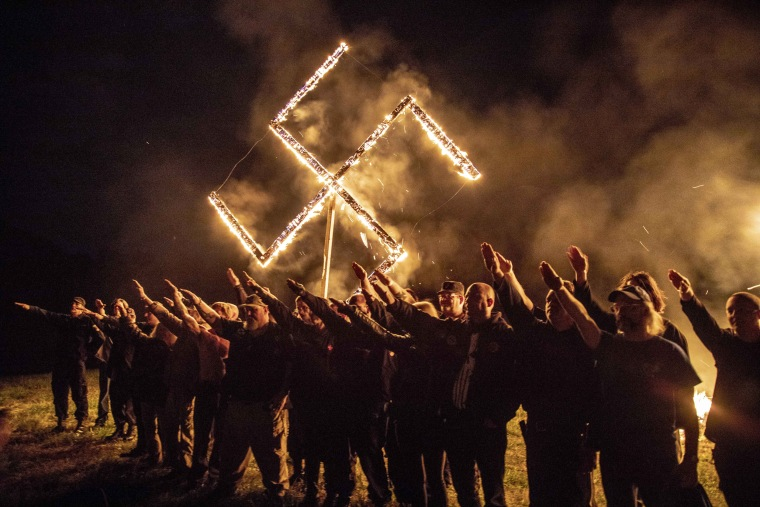 Image: Members of the National Socialist Movement hold a rally and swastika lighting ceremony