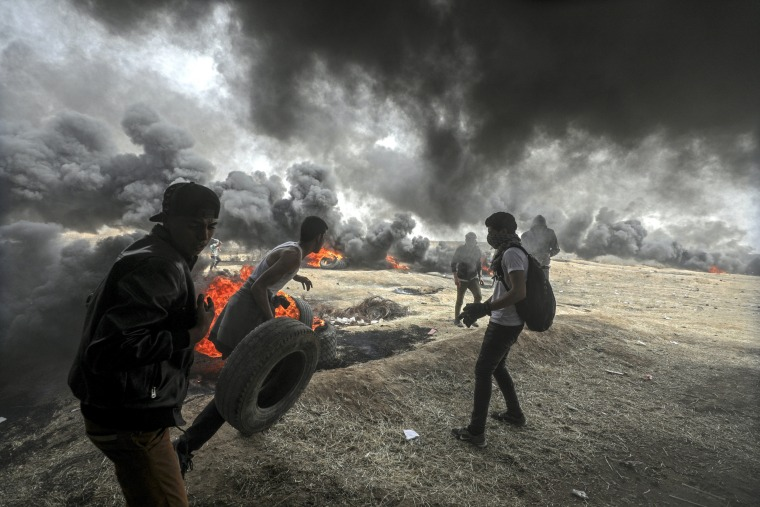 Image: Palestinians protesters burn tires during clashes near the border with Israel