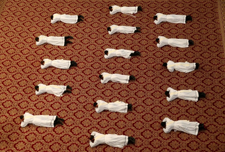 Image: Newly ordained priests lie on the floor as Pope Francis leads a mass in Saint Peter's Basilica