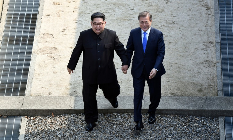 Image: Kim Jong Un and Moon Jae-in cross the military demarcation line at Panmunjom, Friday.