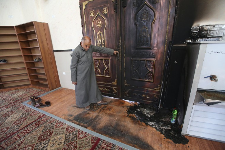 Image: A Palestinian man looks damage from a fire at the Shekh Sade mosque in the West Bank village of Aqraba
