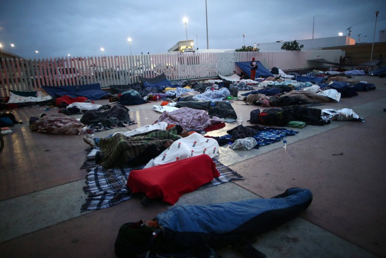 Image: Members of a caravan of migrants from Central America sleep near the San Ysidro checkpoint in Tijuana