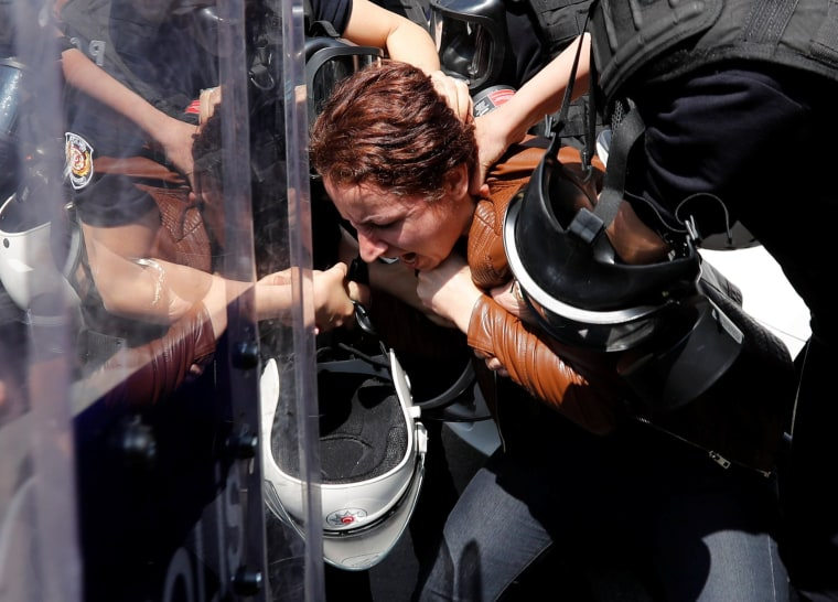 Image: Turkish riot police detain a protester as she and others attempted to defy a ban and march on Taksim Square to celebrate May Day in Istanbul