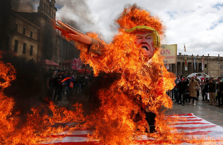 Image: Protesters burn cutout depicting Trump during May Day rally in Bogota