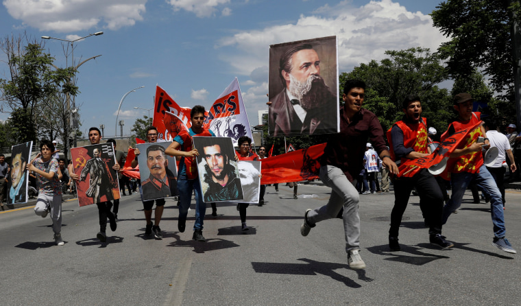 Image: Protesters hold banners, flags and shout slogans during a May Day rally in Ankara